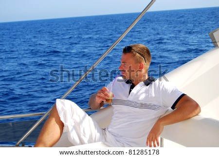 Young Sailor relaxing happily on the vacation sailboat yacht and drinking cold frappe having a rest on summer boat over blue ocean background