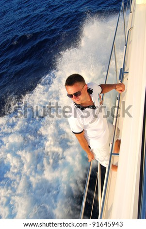 Young Sailor relaxing happily on the vacation sailboat yacht standing on a deck  having a rest on summer boat over blue ocean wave splashes background