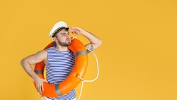 Young sailor with ring buoy on yellow background