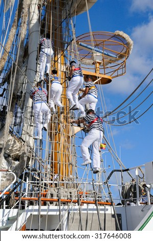 Young sailors of a ship school, climbing the masts.