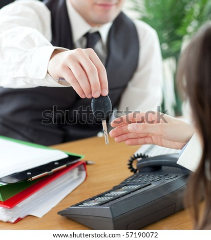 Young salesman giving car\'s key to his customer in his office