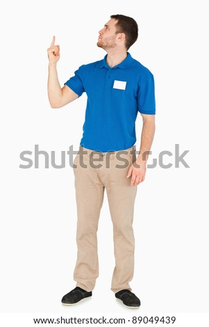 Young salesman looking and pointing upwards against a white background