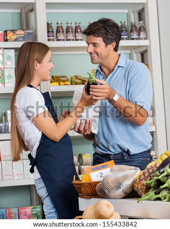Young saleswoman assisting male customer in buying vegetables at supermarket