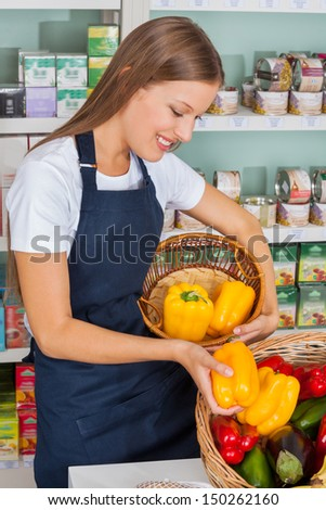 Young saleswoman choosing bellpeppers in grocery store