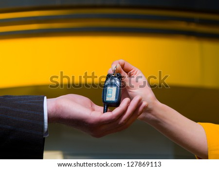 Young saleswoman handing a car key to a customer.