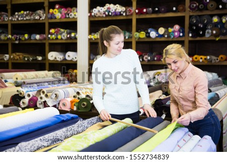 Young saleswoman of tissue store consulting female buyer about new trendy fabrics for dressmaking
