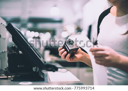 Young saleswoman taking a stamp with discount / sale to receipt (color toned image) #775993714