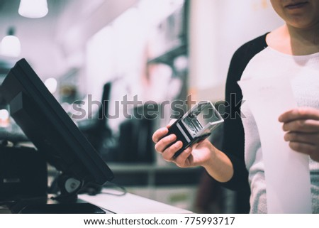 Young saleswoman taking a stamp with discount / sale to receipt (color toned image)