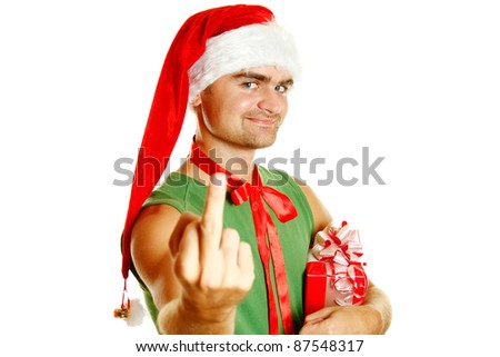 Young Santa holding a gift box hat on his head shows a frame obscene sign. Rude gestures