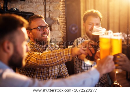 Young satisfied bearded men celebrating and toasting with a beer in the sunny pub after work. #1072229297
