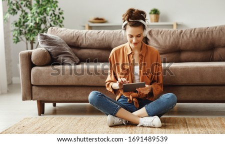 Young satisfied female in casual clothes and wireless headphones surfing digital tablet while sitting on floor with legs crossed near soft couch in light modern living room