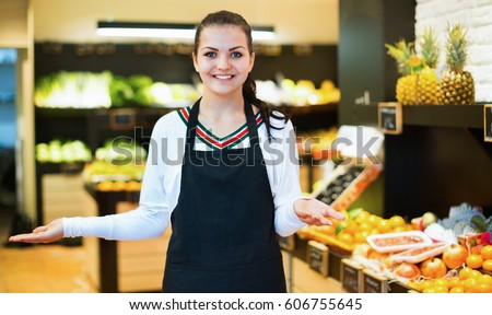 Young satisfied  shopping assistant demonstrating assortment of grocery shop #606755645