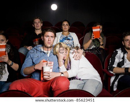 Young scared couple at the movie theater