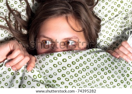 Young scared girl hiding under blanket