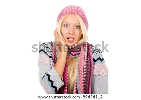 young scared, terrified woman looking at camera holding hand on face, wear winter knitted pink hat scarf and sweater, isolated over white background