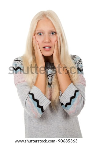 young scared, terrified woman looking at camera holding hand on face, wear winter knitted  sweater, isolated over white background