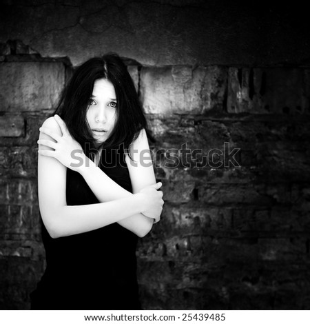 Young scared woman portrait. Black and white concept.