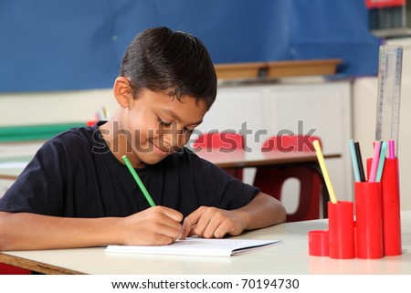 Young school boy age ten writing at his classroom desk - stock photo