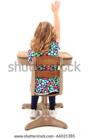 Young school girl in desk with hand raised over white background.