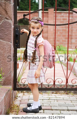 Young school girl in uniform with pink backpack goes to school