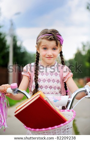 Young school girl rides her pink bike to school