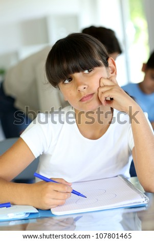 Young school girl with bored look on her face