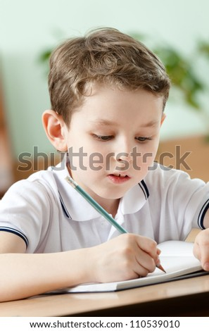 Young schoolboy does some notes with pen on the sheet of paper, close up