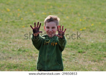 young schoolboy showing dirty hands against green blurred background, outside