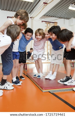 Young schoolboys in gym having a huddle