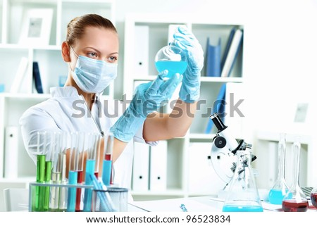 Young scientist in white uniform working in laboratory - stock photo