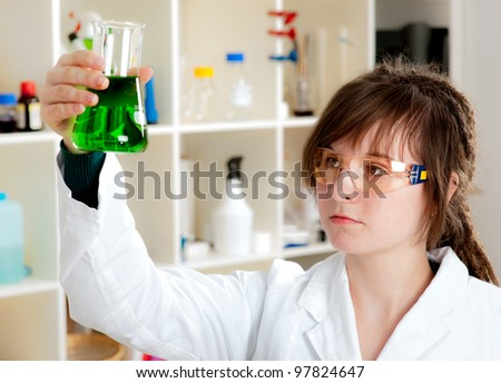 Young scientist mixes green liquid in a conical flask