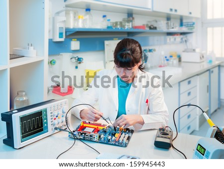 Young scientist repairs electronic device in modern laboratory Foto stock ©