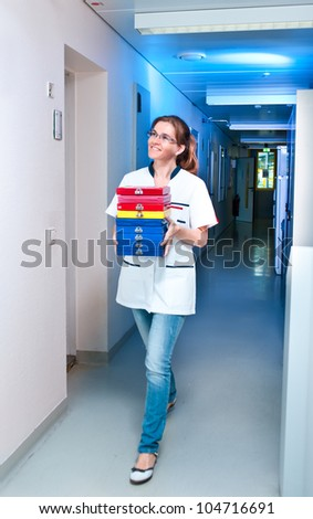 Young scientist walks down the corridor carrying histological samples