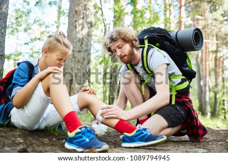 Young scout helping his friend with bandage to bind up injury on leg on their way to camp
