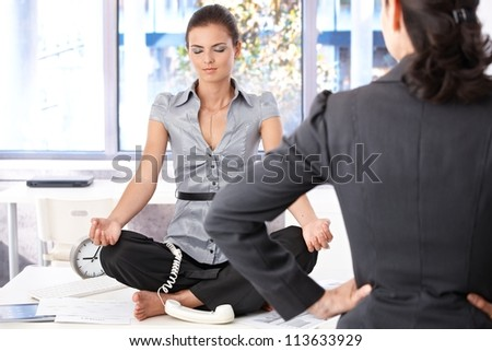 Young secretary meditating in office on top of desk, angry boss looking at her.