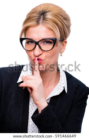 Young secretary requires silence. Young beautiful blonde woman has put forefinger to lips as sign of silence, on white wall background