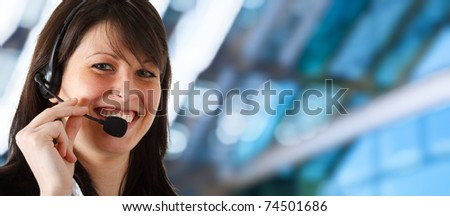 Young secretary smiling while helping a customer. Blue blurred background.