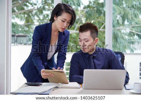 Young secretary with digital tablet consulting with businessman while he working on laptop computer at office stock photo