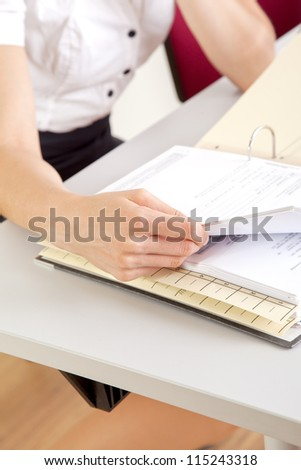 young secretary working in office with file folder