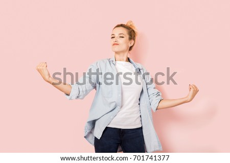 Young self-confident woman on a pink background
