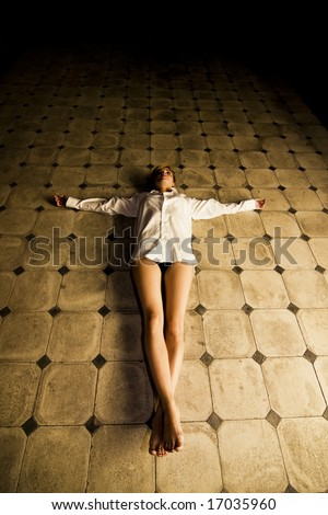 Young seminude crucified woman on the floor - stock photo