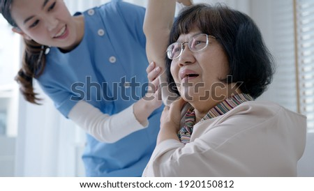 Young senior asia citizen female with scrubs nurse physiotherapy worker at home in rehabilitation therapy service for aging parents. Massage for older care, ache pain joints exercise in old people. Stock photo ©
