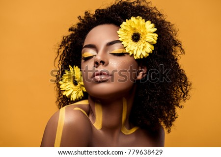 Young sensual african american woman with artistic make-up and gerbera in hair isolated on orange background #779638429