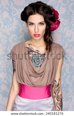 Stock Photo Young sensual attractive sexy european brunette girl with beautiful tattoo on her chest and arms posing for fashion photo shoot with red rose in her long hair in front of color floral background