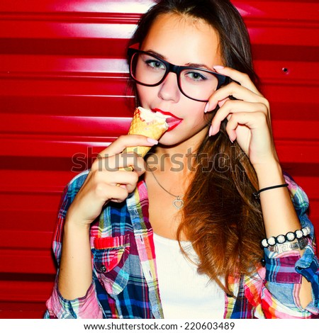 Young sensual sexy brunette fashion woman closeup portrait eating vanilla ice-cream corn on red background in the night
