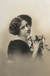 young sentimental woman with flowers. vintage picture ca. 1910
