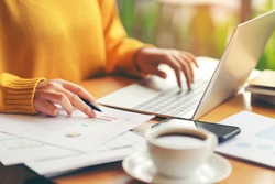Young serious accountant woman checking paperwork from accounting department to analyse number on document, using laptop check business database, information comparing. Typing keyboard for recording