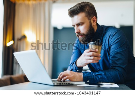 Young serious bearded businessman working on computer at table,drinking coffee.Man analyzes information, data, develops business plan. Freelancer, entrepreneur.Online marketing, education, e-learning.