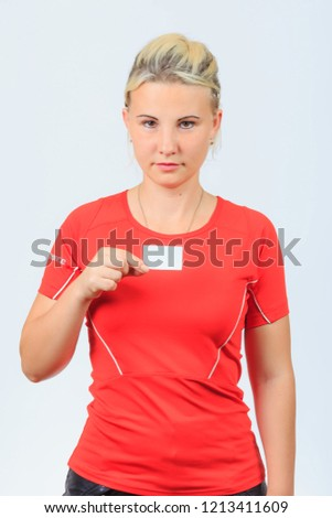 37366b80 Young serious blonde girl in red shirt and black shorts holds blank  business card with copyspace