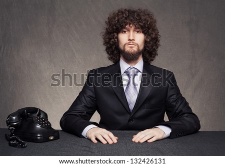 young serious businessman and and a vintage telephone on grunge background